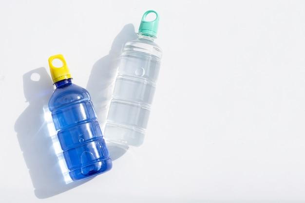 Botellas de agua de plástico sobre superficie blanca