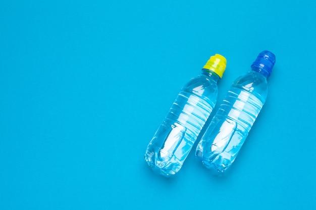 Botellas de agua de plástico con tapas de diferentes colores sobre la mesa.