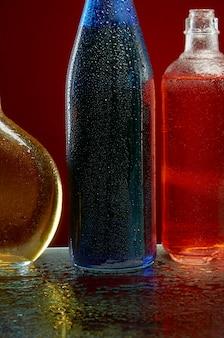 Botellas de alcohol en gotas de agua en rojo