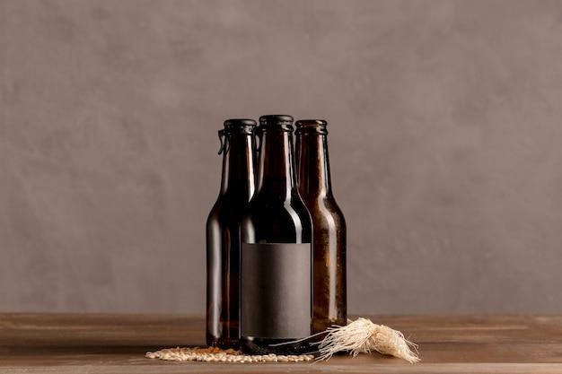 Botellas alcohólicas marrón en etiqueta gris en mesa de madera