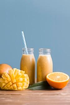 Botellas de batido de vista frontal con mango y naranja