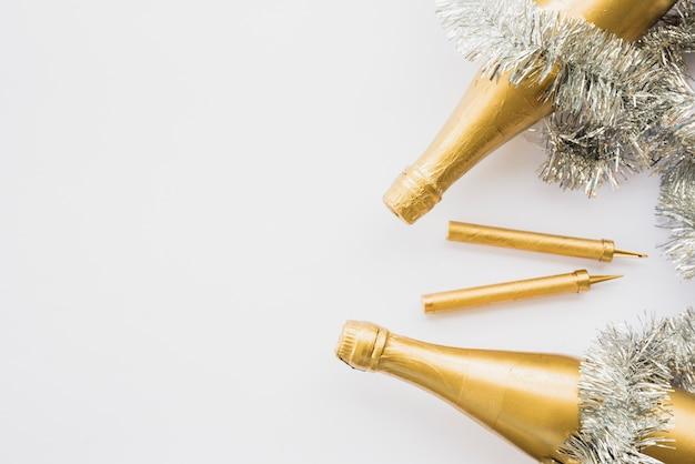 Botellas de bebida cerca de oropel y bengalas de fuegos artificiales.