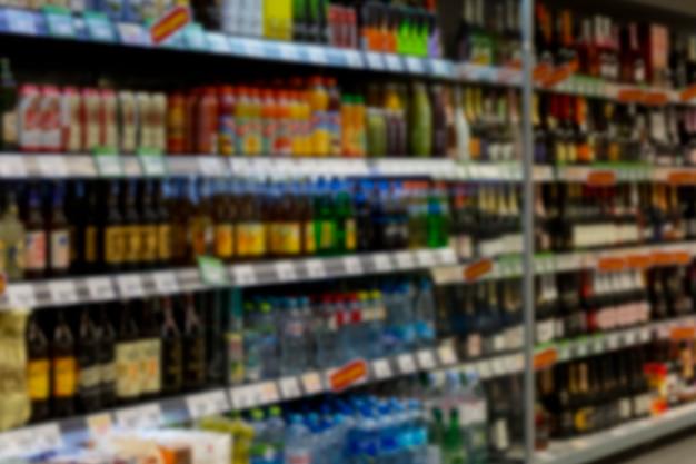 Botellas de bebidas en los estantes del supermercado. borroso.
