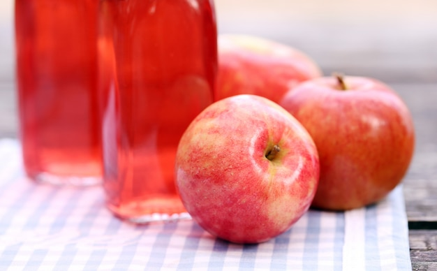 Botellas con bebidas rojas y algunas manzanas.