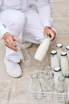 Botellas cambiantes de lechero irreconocible