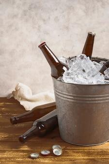 Botellas de cerveza de alto ángulo en la mesa y dentro del cubo con hielo