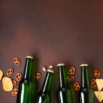 Botellas de cerveza y aperitivos sobre fondo oscuro