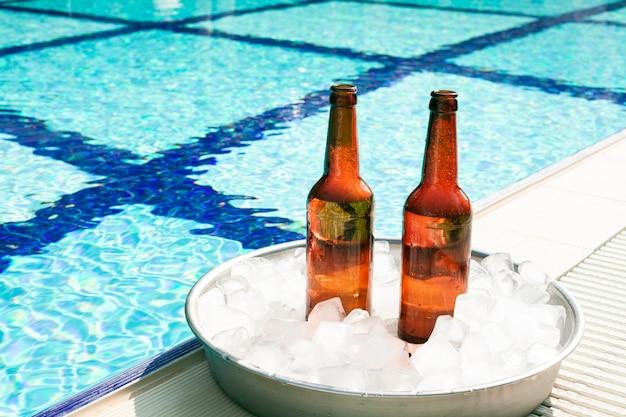Botellas de cerveza en bandeja con hielo