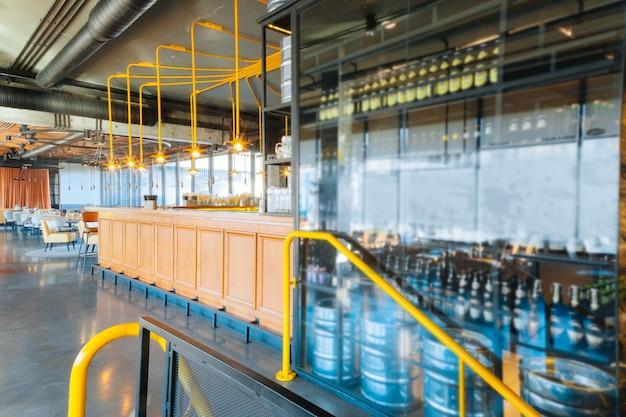 Botellas de cerveza botellas de cerveza oscura artesanal situadas cerca de la pared de vidrio y el soporte de la barra