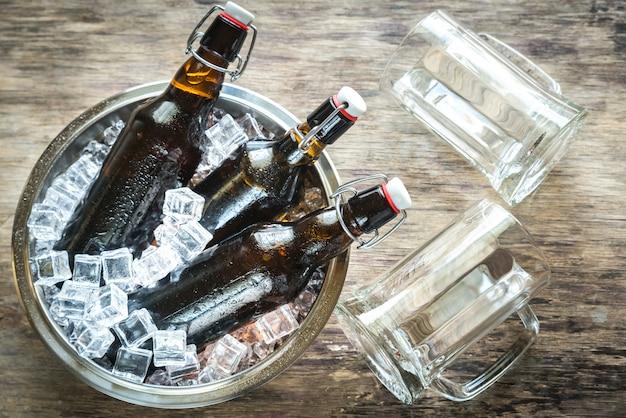 Botellas de cerveza en cubitos de hielo.