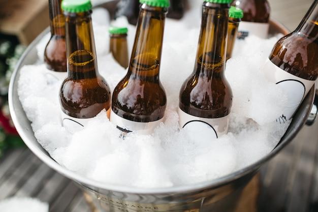 Las botellas con cerveza se enfrían en un cubo con hielo