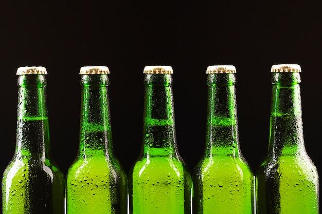 Botellas de cerveza fría de pie en una fila.