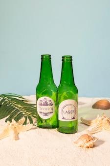 Botellas de cerveza en la playa con conchas
