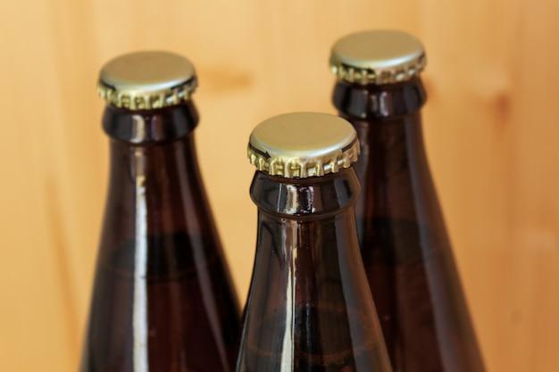 Botellas de cerveza, primer plano de bebidas refrigeradas, sobre fondo de madera