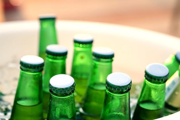 Botellas de cerveza verde se enfrían en un cubo de hielo.