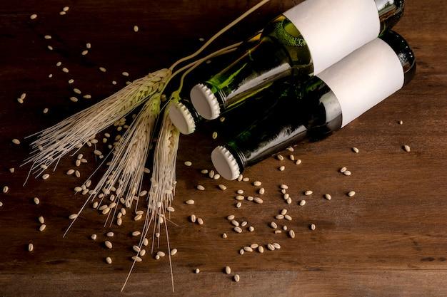 Botellas de cerveza verde y espiga de trigo y en mesa de madera