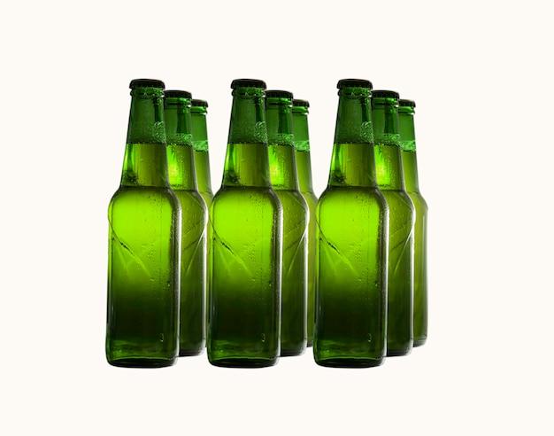 Botellas de cerveza verde en filas aisladas sobre fondo blanco.