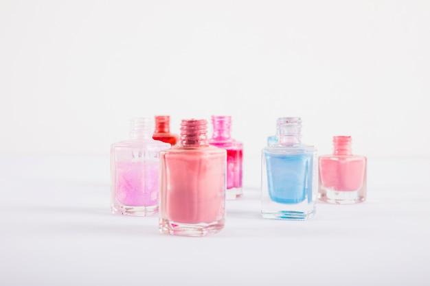 Botellas coloridas del esmalte de uñas en la superficie blanca