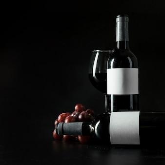 Botellas y copa de vino cerca de la uva
