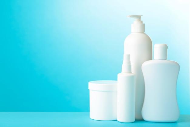 Botellas cosméticas blancas sobre fondo azul con espacio de copia. vista superior