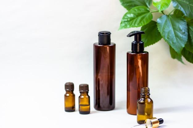 Botellas cosméticas oscuras y hojas verdes naturales sobre un fondo claro