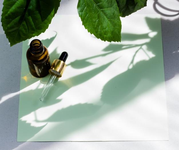 Botellas cosméticas oscuras y hojas verdes naturales.