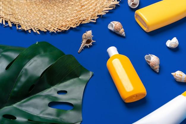 Botellas con cosméticos bloqueadores solares y conchas marinas sobre fondo azul oscuro
