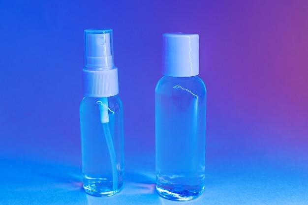 Botellas de cosméticos con loción transparente en luz de neón brillante de moda.