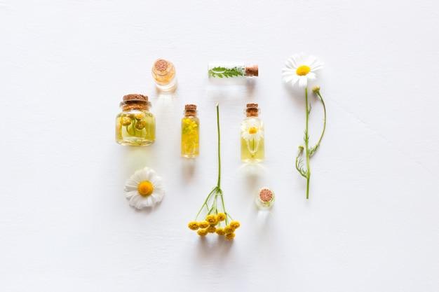 Botellas con cosméticos naturales para el cuidado de la cara y el cuerpo y flores silvestres en blanco