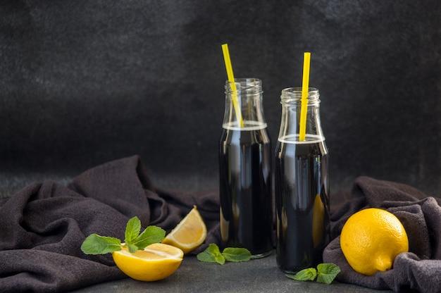 Botellas con desintoxicación de carbón negro limonada en la mesa