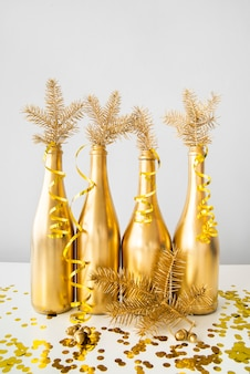 Botellas doradas con cintas y hojas de pino.