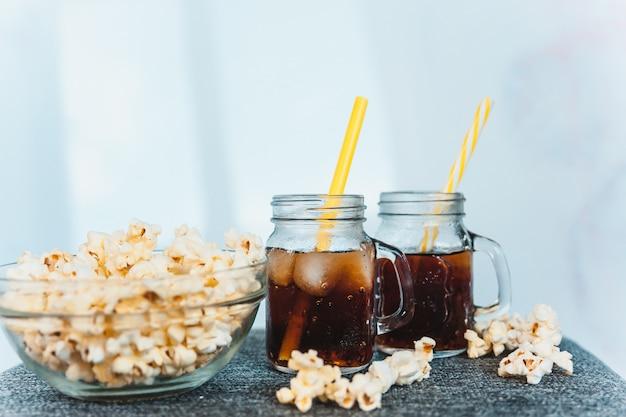 Botellas empañadas de cola con hielo y caldera fresca de maíz