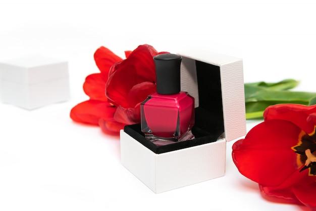 Botellas de esmalte de uñas de color rosa y flores de tulipán sobre fondo blanco.
