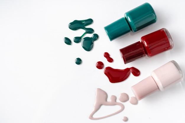 Botellas de esmalte de uñas de colores brillantes con goteos sobre fondo blanco.