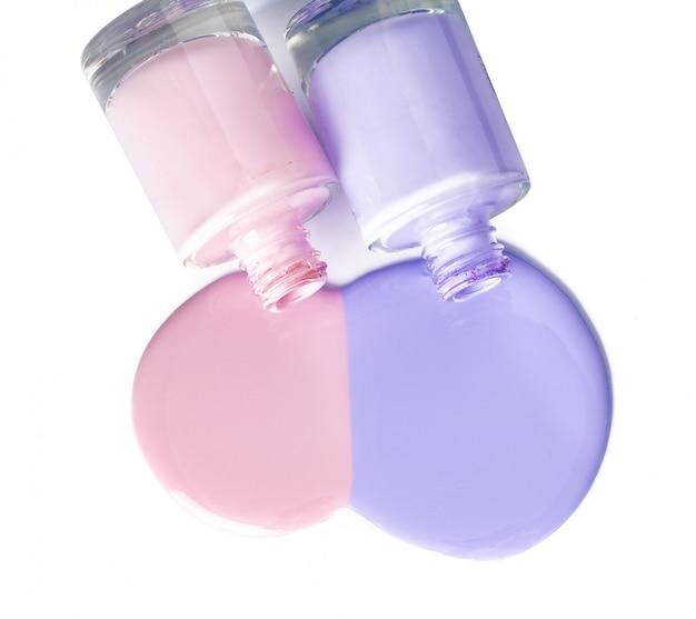 Botellas de esmalte de uñas derramadas de color pastel sobre blanco