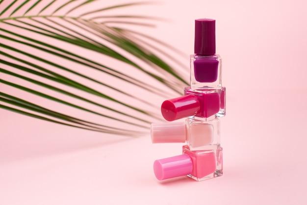 Botellas con esmalte de uñas sobre pared rosa