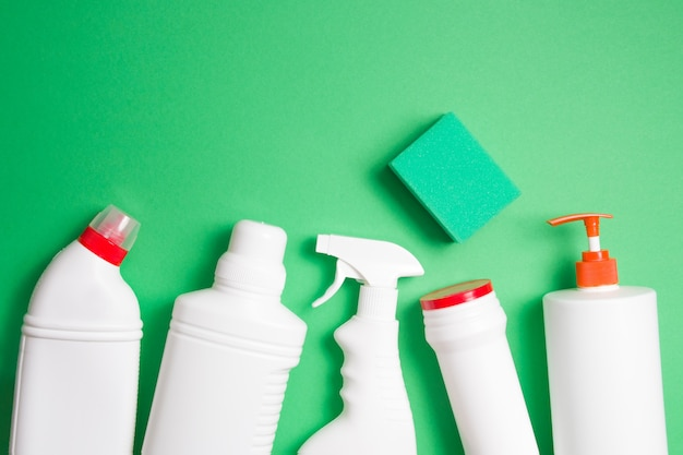 Botellas de esponja y detergente sin etiquetas en un espacio de copia de vista superior de fondo verde