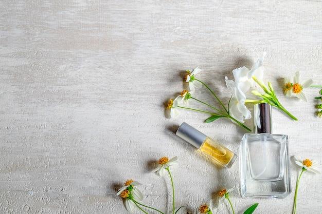 Botellas y flores de perfume en un fondo de madera blanco