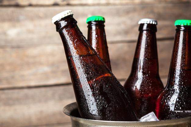 Botellas frías de cerveza en el cubo en madera