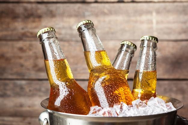 Botellas frías de cerveza en un cubo