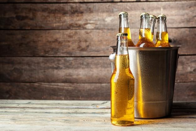 Botellas frías de cerveza en el cubo