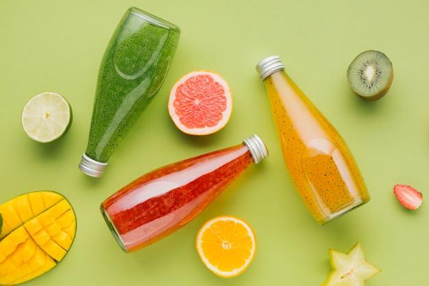 Botellas de jugo de colores y rodajas de fruta