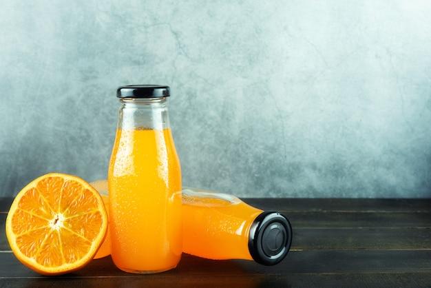 Botellas de jugo fresco de naranja y rebanada naranja alta vitamina c refrescante bebida de verano en mesa de madera con espacio de copia