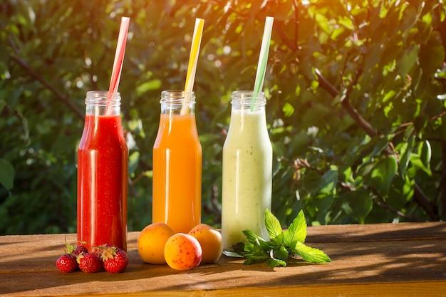 Botellas con jugo y frutas, concepto de comida. verano luz del sol