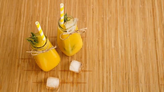 Botellas de jugo de naranja y pajitas de papel. bebida helada en un día soleado