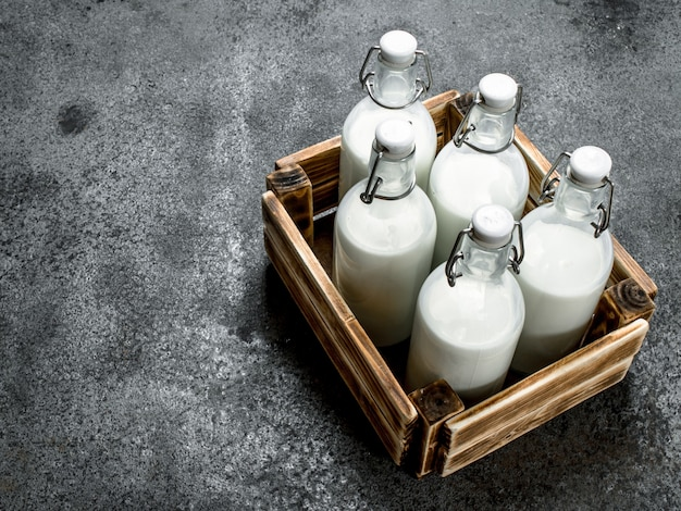 Botellas de leche fresca en una caja vieja. sobre un fondo rústico.