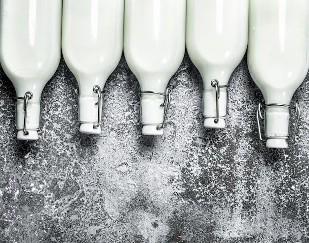 Botellas de leche fresca. sobre un fondo rústico.