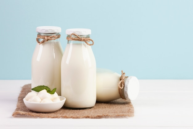 Botellas de leche y mozzarella sobre tela de arpillera.