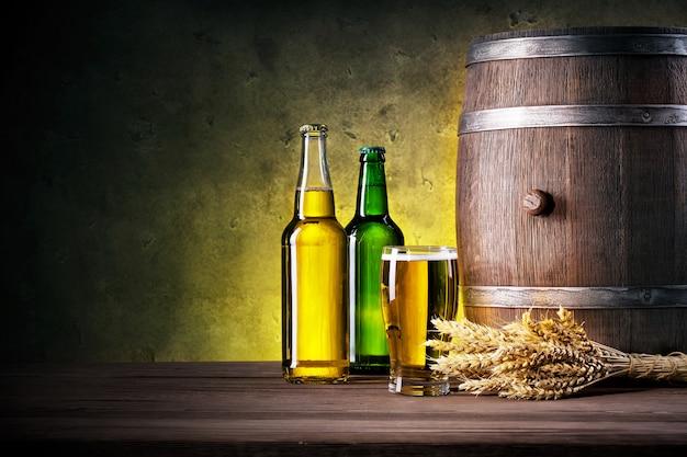 Botellas llenas de cerveza y vaso con barril