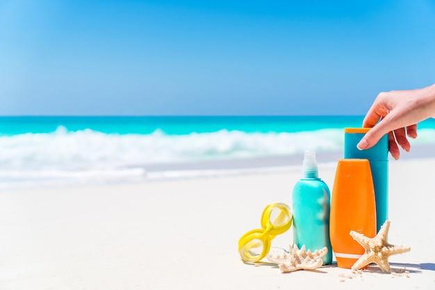 Botellas de loción bronceadora y estrellas de mar en la playa